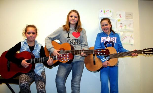 Emma Solberg, Solveig Grebstad Aas og Lovise Hunnes Hanssen får gitarundervisning i Sykkylven musikk- og kulturskule. -Vi lærer å spele mange songar. Det er ein bra følelse å få det til, seier jentene. (Foto: Hanne Suorza)